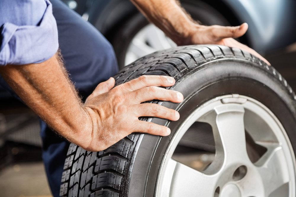 man's hands rolling tire performing auto repair service